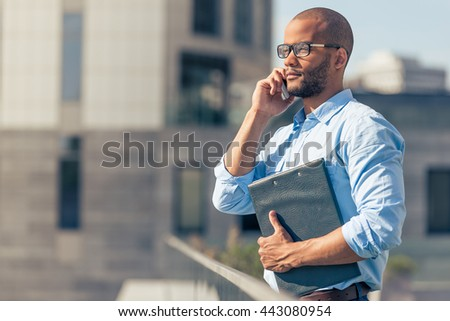 Handsome young Afro American businessman in eyeglasses is talking on the mobile phone and holding a folder, standing outdoors - stock photo