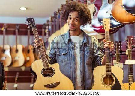 Handsome young Afro-American man holding two guitars in both hands and smiling while standing in a musical shop - stock photo