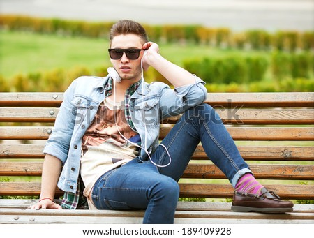 Handsome young American man smiling and listening to music on his earphones