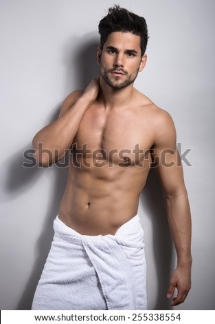 handsome young and fit bodybuilder after shower showing of his perfect body and six pack - stock photo