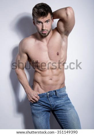 handsome young and fit bodybuilder posing shirtless on grey background