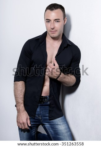 handsome young and fit bodybuilder posing with open shirt - stock photo