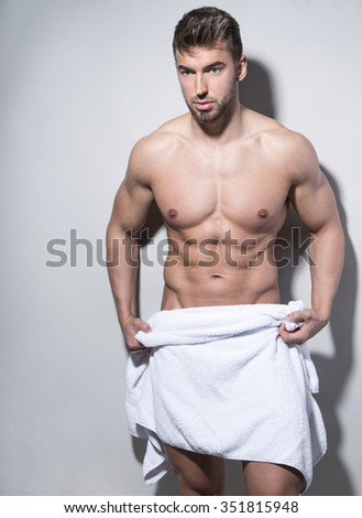 handsome young and fit bodybuilder with towel after shower