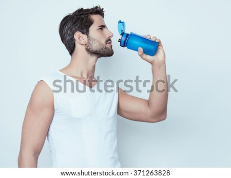 handsome young and fit man in workout clothes - stock photo