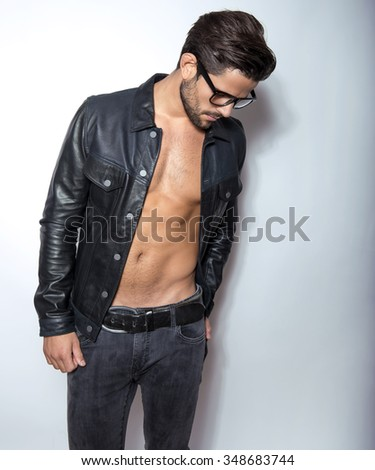 handsome young and fit man posing with open jacket - stock photo