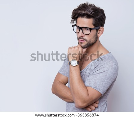 handsome young and fit man with glasses and wrist watch posing on grey background - stock photo