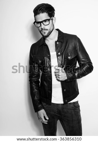 handsome young and fit man with glasses posing on grey background
