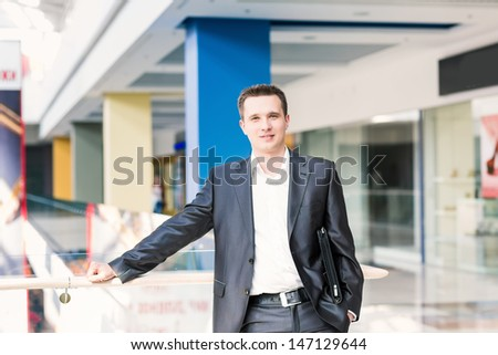 Handsome young and successful businessman in a shopping center - stock photo
