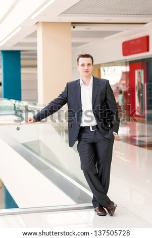 Handsome young and successful businessman standing in a shopping center - stock photo