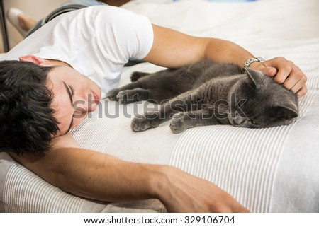Handsome Young Animal-Lover Man on a Bed, Hugging and Cuddling his Gray Domestic Cat Pet. - stock photo