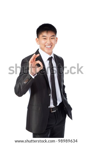 Handsome young asian business man hold hand with ok gesture sign, businessman happy smile, wear elegant suit and tie isolated over white background