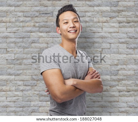 Handsome young asian man crossing his arms and smiling - stock photo