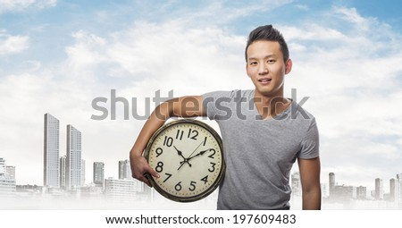 handsome young asian man holding a clock