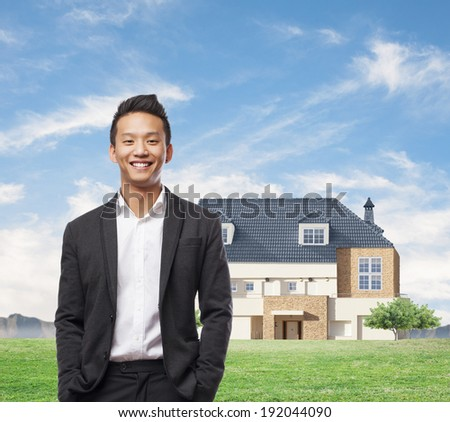 handsome young asian man in front of his house - stock photo
