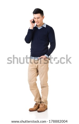 Handsome young Asian man take a call, full length portrait isolated on white background. - stock photo