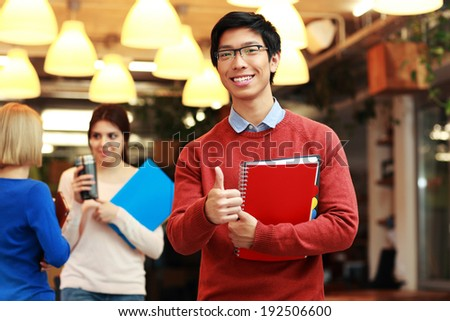 Handsome young asian student doing thumbs up in front of a group of students - stock photo