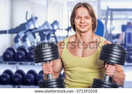 Handsome young athlete in the gym with heavy weights - stock photo