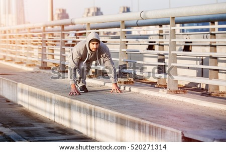 Handsome young athlete man  is ready to run. Runner jogging over bridge road. Fitness concept. Toned photo.