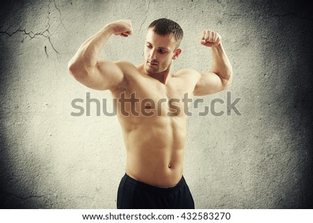 Handsome young athletic muscular bare-chested man is standing isolated over concrete wall and showing biceps on both arms