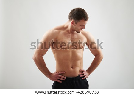Handsome young athletic muscular bare-chested man is standing isolated over white background and looking down at his left arm