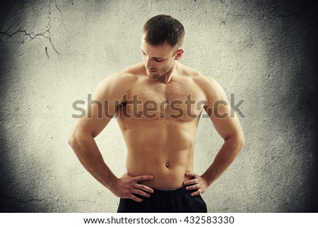 Handsome young athletic muscular man with bare chest is standing isolated over old concrete wall and looking down, hands on hips