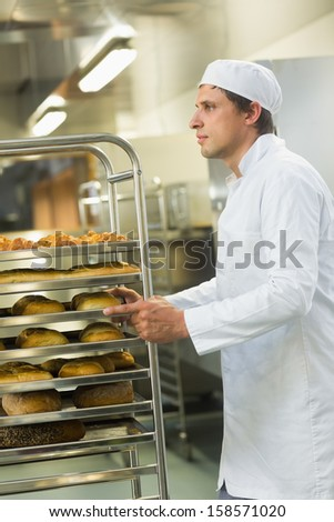 Handsome young baker pushing a trolley with food on it