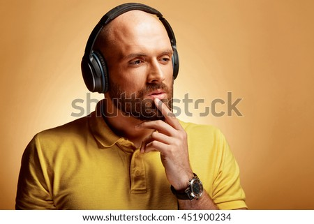 Handsome young bald man with thinking face and earphones - stock photo