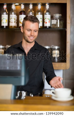 Handsome young barista gesturing at counter in coffeeshop - stock photo