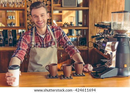 Handsome young barista in apron is giving a cup of coffee, looking at camera and smiling while standing at the bar counter at cafe - stock photo