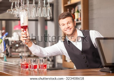 Handsome young bartender is preparing alcohol drinks. He is standing and holding bottle. The man is pouring red beverage into glass. He is looking at camera and smiling - stock photo