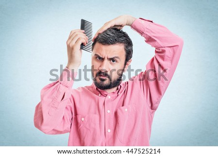 Handsome young beard man combing his hair