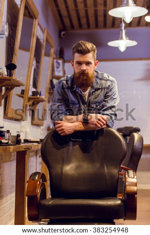 Handsome young bearded barber leaning on a chair and looking at camera while standing in the barber shop - stock photo