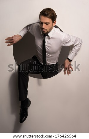 Handsome young bearded businessman climbing out of a circular hole in a white wall in a conceptual image - stock photo
