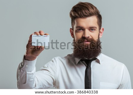 Handsome young bearded businessman in classic white shirt is showing a business card and smiling, on a gray background - stock photo