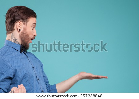 Handsome young bearded hipster is showing something with surprise. He is standing and raising arm sideways. Isolated and copy space in right side - stock photo