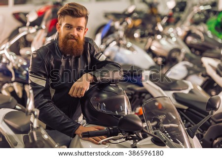 Handsome young bearded man in black leather jacket is holding a helmet, looking at camera and smiling while sitting on a motorbike