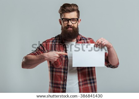 Handsome young bearded man in casual clothes and eyeglasses is holding a sheet of paper and pointing on it, on a gray background - stock photo