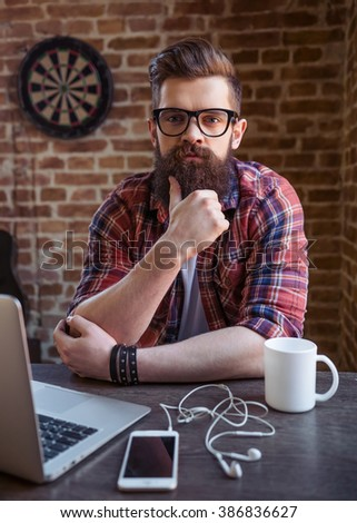 Handsome young bearded man in casual clothes and eyeglasses is using a laptop and looking at camera while working