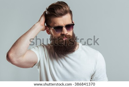 Handsome young bearded man in sunglasses is smoothing his hair and looking at camera, on a gray background - stock photo