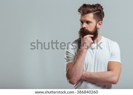 Handsome young bearded man is keeping hand on beard and looking away, on a gray background - stock photo