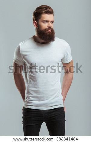 Handsome young bearded man is looking away while standing against gray background - stock photo