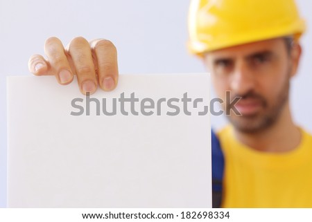 Handsome young bearded workman in a yellow hardhat and matching t-shirt holding empty page document - stock photo