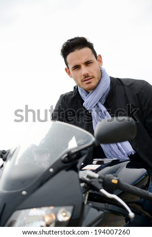 handsome young biker man riding a black motorbike with sunglasses