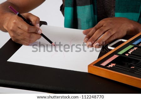 handsome young black man drawing with colored pastels as he designs clothing - stock photo