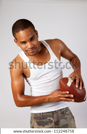 handsome young black man holding a football  with thoughtful, and serious eye contact