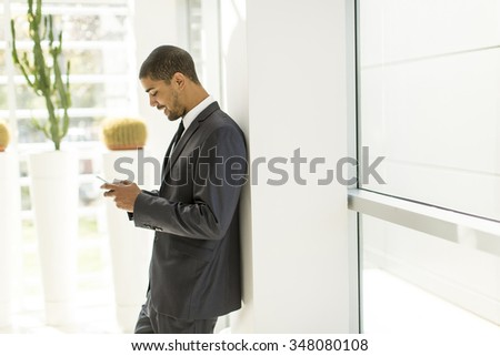 Handsome young black man with mobile phone in the office - stock photo