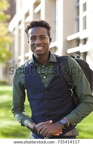 Handsome young black student man with backpack smiles on college campus