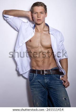 handsome young bodybuilder showing of his fit body and muscles - stock photo