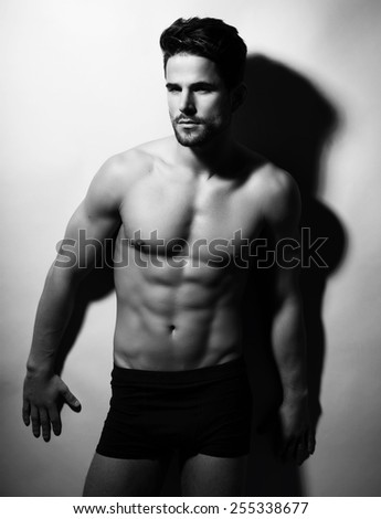 handsome young bodybuilder with fit, perfect body and six pack posing in studio