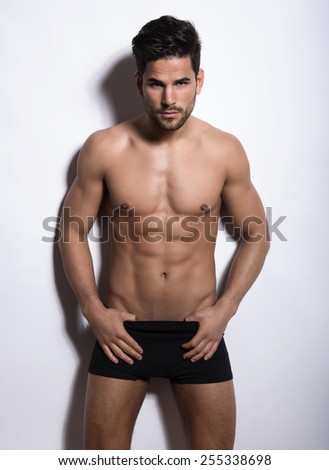 handsome young bodybuilder with fit, perfect body and six pack posing in studio - stock photo